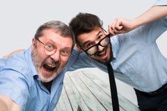 Deux collègues portant à la photo leur l'individu s'asseyant dans le bureau Photo libre de droits