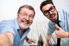 Deux collègues portant à la photo leur l'individu s'asseyant dans le bureau Photos stock
