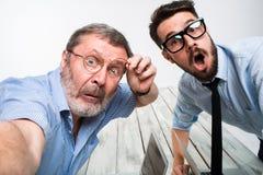 Deux collègues portant à la photo leur l'individu s'asseyant dans le bureau Photographie stock