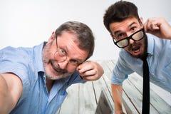 Deux collègues portant à la photo leur l'individu s'asseyant dans le bureau Image libre de droits
