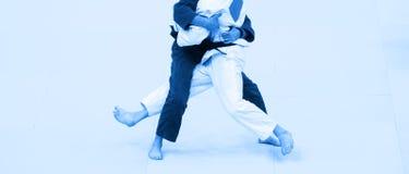 Deux combattants de judo dans l'uniforme blanc et bleu Filtr bleu de couleur image stock