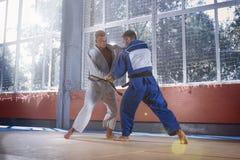 Deux combattants de judo montrant la qualification technique tandis que les arts martiaux de pratique dans un combat matraquent photo stock