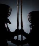 Deux combattants foncés de kendo vis-à-vis de l'un l'autre Image libre de droits