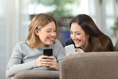 Deux compagnons de chambre parlant du contenu sur leurs smartphones Photo libre de droits