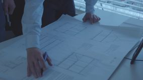 Deux concepteurs d'architecte travaillant avec le projet architectural de la nouvelle maison au bureau barre Plan rapproch? banque de vidéos