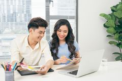 Deux concepteurs occasionnels de sourire travaillant avec l'ordinateur portable tout en reposant a Image libre de droits