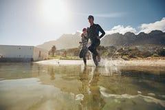Deux concurrents dans des vêtements isothermiques fonctionnant dans l'eau Photo stock