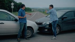 Deux conducteurs argumentent au sujet du blâme pour l'accident par le côté d'endommagé Deux conducteurs masculins discutent au su clips vidéos