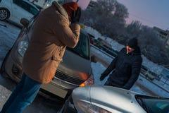 Deux conducteurs masculins bouleversés regardant les voitures endommagées Photo stock