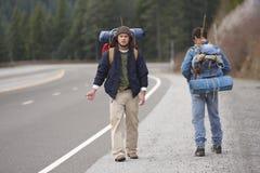 Deux copains campants faisant de l'auto-stop Photos stock