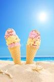 Deux cornets de crème glacée ont collé dans le sable sur une plage Images stock