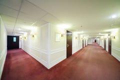 Deux couloirs légers spacieux avec beaucoup de portes en bois image stock