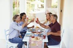 Deux couples à une table de dîner sur un patio soulèvent leurs verres Images stock