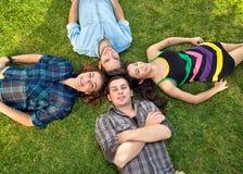 Deux couples adolescents détendant sur l'herbe Photo stock