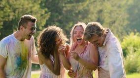 Deux couples affectueux obtenant éclaboussés avec de l'eau après combat coloré de peinture de poudre clips vidéos