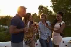 Deux couples appréciant des boissons sur un dessus de toit au coucher du soleil, Ibiza Photos libres de droits