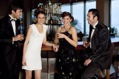 Deux couples au bar buvant et flirtant Photographie stock libre de droits