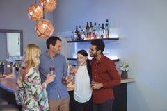Deux couples ayant des cocktails ensemble Images stock