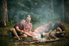 Deux couples ayant le pique-nique en bois Homme barbu et son meilleur ami faisant cuire des saucisses au-dessus du feu Jeunes ran Photo stock