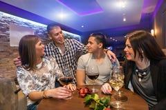 Deux couples célébrant en café Photographie stock libre de droits