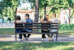 Deux couples d'amants se reposant sur différentes extrémités d'un banc Photographie stock libre de droits
