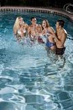 Deux couples dans la piscine la nuit Photo libre de droits