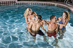 Deux couples dans la piscine la nuit Image stock