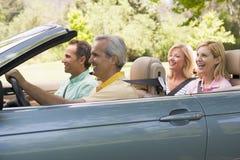 Deux couples dans le sourire convertible de véhicule Photographie stock libre de droits