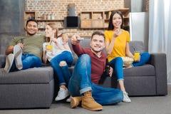 Deux couples de détente se reposant ensemble et TV de observation Image stock