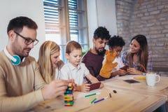 Deux couples de métis jouent les jeux éducatifs avec leurs enfants Photographie stock libre de droits