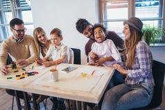 Deux couples de métis jouent les jeux éducatifs avec leurs enfants Image libre de droits