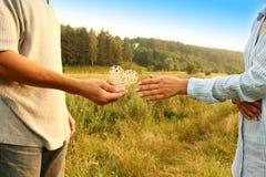 Deux couples de mains d'amour sur la nature Photos stock