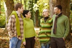 Deux couples parlant dans la forêt d'automne Photographie stock