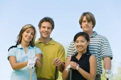 Deux couples des golfeurs posant sur le terrain de golf Image stock