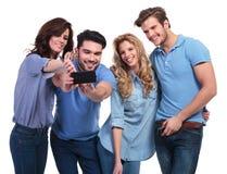 Deux couples des jeunes prenant leur photo avec le téléphone Image libre de droits