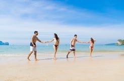 Deux couples des vacances d'été de plage, les jeunes dans l'amour marchant, femme d'homme tenant l'océan de mer de mains Images stock