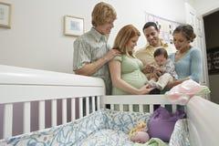 Deux couples et bébé par le berceau Photos libres de droits