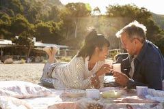 Deux couples ferroutant à la plage, regardant l'un l'autre Images stock