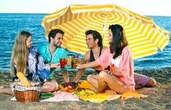 Deux couples grillent sous un parapluie sur la plage Photo libre de droits