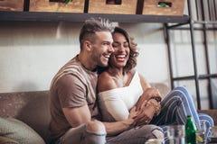 Deux couples heureux de métis ayant l'amusement au café Image stock