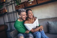 Deux couples heureux de métis ayant l'amusement au café Photos stock