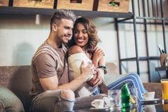 Deux couples heureux de métis ayant l'amusement au café Image libre de droits