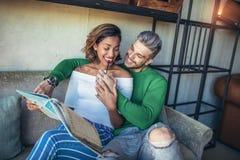 Deux couples heureux de métis ayant l'amusement au café Photographie stock libre de droits