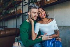 Deux couples heureux de métis ayant l'amusement au café Photo stock