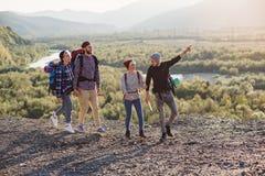 Deux couples heureux marchant dans les montagnes avec la carte Jeune homme caucasien avec la carte choisissant la bonne direction photos libres de droits
