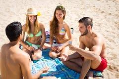 Deux couples jouant des cartes sur la plage Photographie stock