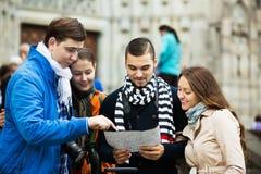 Deux couples lisant la carte de ville Photographie stock