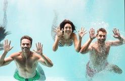Deux couples nageant sous l'eau dans la piscine Photos libres de droits