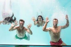 Deux couples nageant sous l'eau dans la piscine Photo stock