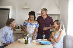 Deux couples préparant la nourriture et buvant du vin, vue de face Photographie stock